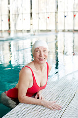 Cheerful mature female in red swimsuit and white rubber cap spending leisure in swimming pool