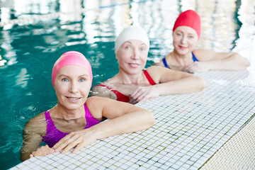 Group of mature women in swimwear sitting in swimming-pool and looking at you