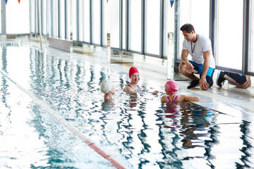 Three happy females in swimwear having talk in water while their trainer consulting them