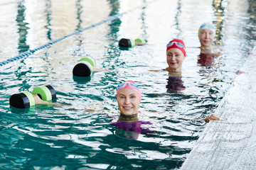 Row of happy senior females in swimwear outstretching their right arms while lifting barbells during workout in water