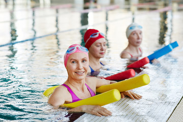 Active senior women in swimwear holding equipment for water aerobics while training in swimming-pool
