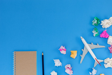 Airplane model with blank paper note on blue background, picture for add text message or used background, website, travel and tour background.