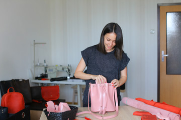 Woman standing with pink handmade leathe woman bag and wallet a atelier. Concept of handicraft goods and home business.