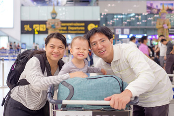 Asian family with cute 18 months / 1 year old toddler baby boy child in airport before boarding at Suvarnabhumi Airport (Bangkok public international airport), Family travel, vacation with kid concept