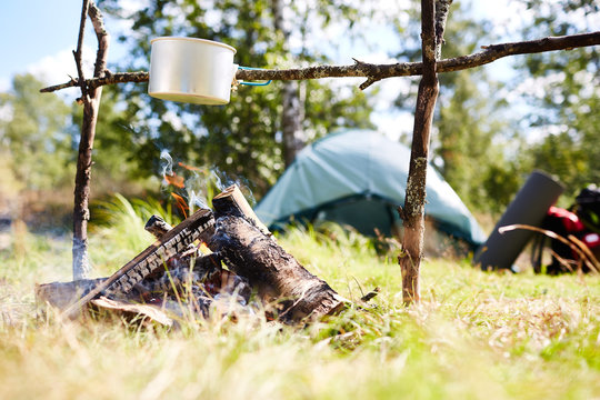 Small aluminum pan hanging on stick over campfire where food for backpackers is being cooked