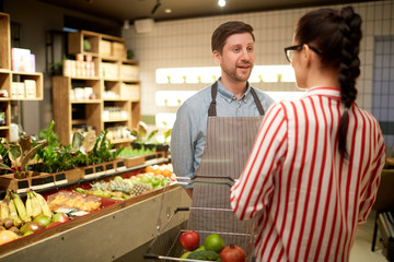 Young assistant in uniform consulting buyer of supermarket about what to choose