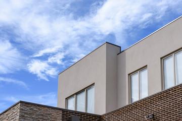Modern residential property against blue sky background.