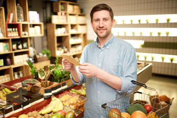 Happy buyer with shopping list and basket with vegs looking at camera in supermarket