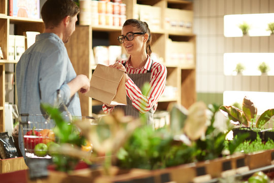 Happy shop assistant giving paper pack to man who chose something in supermarket