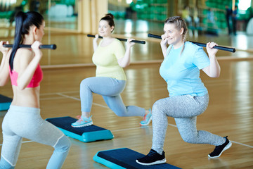Two young active women with gymnastic bars exercising on step-platforms with their fitness trainer...