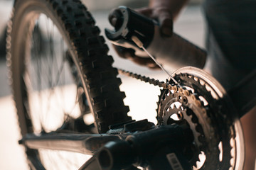 A guy athlete serves and repairs his mountain bike in the garage