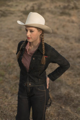 Vintage 1950s cowgirl in jeans in field.