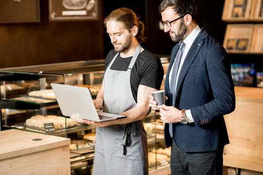 Businessman and barista working in the pastry shop