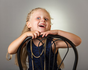 Smiling girl with long hair in dress with beads sitting on chair, on grey