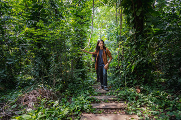 male travelers walking through jungle. two man hiking in forest dense. concept of Travel relax, Holiday and vacation..
