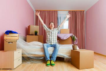 Image of happy woman sitting on sofa among cardboard boxes