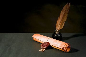 Scroll of a papyrus with a seal, a feather and an inkwell