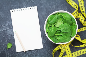 Clean notebook, green spinach leaves and tape measure top view. Diet and healthy food concept.