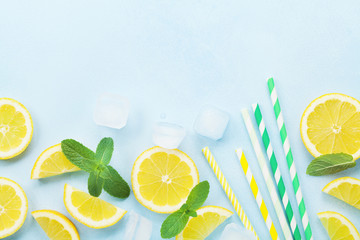 Lemon slices, ice, colorful straw and mint leaves on blue table top view. Ingredients for summer cocktail and lemonade. Flat lay.