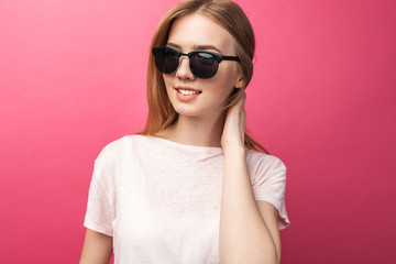 Beautiful young blonde girl in glasses standing on pink background wearing jeans, pink top smiling snow white smile, wearing black glasses and looking perfect promotional photo