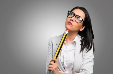 Pretty woman with glasses holding a big pencil on grey background