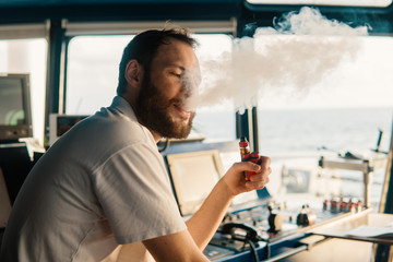 Deck navigation officer smokes a wad on the navigation bridge of yacht. wyper relax with big smoke