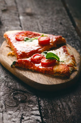 Italian food, cuisine. Margherita pizza on a black, wooden table with igredients like tomatoes, salad, cheese, mozzarella, basil. Delicious homemade food.