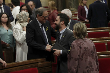 Quim Torra, the candidate proposed by former Catalan leader Puigdemont to head the regional Catalan government, is greeted by Catalan regional parliament speaker, Roger Torrent, after delivering his speech during an investiture debate in Barcelona