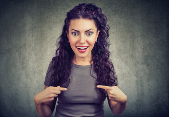 Excited young woman pointing at herself in disbelief of being winner