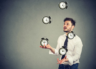 business man juggling his time alarm clocks