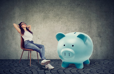woman with big piggy bank relaxing sitting on chair