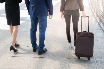 back of businessman and businesswoman walk together with luggage on the public street, business travel concept