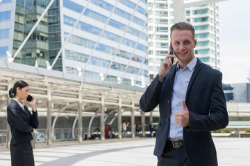business man show thumb up and using mobile phone to talk about business