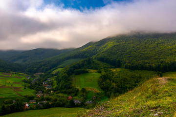 small Carpathian village in mountains. beautiful landscape with forested hills and agricultural fields on a cloudy morning
