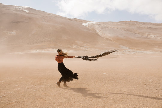 Woman wearing long dress out in a desert dust storm