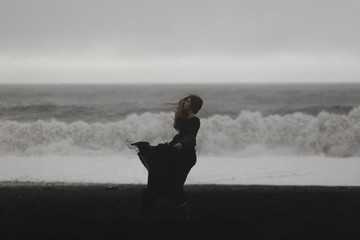 woman wearing a black dress on the black beach in iceland during a storm