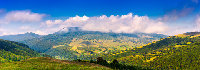 panorama of mountainous rural area in autumn. lovely countryside scenery with fluffy clouds above the ridge