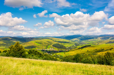 village in the valley of Carpathian mountains. lovely countryside scenery in early autumn with clouds on a blue sky over the distant ridge