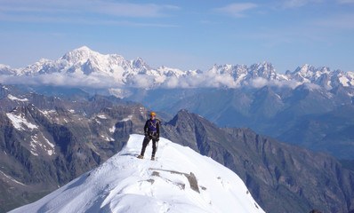 mountain climber on the summit of Gran Paradiso after exiting the north face ascent route with a great view of Mont Blanc behind him