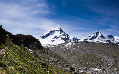 hiking trail leading to snow-capped peaks with a great view of the Gran Paradiso national Park in the Italian Alps