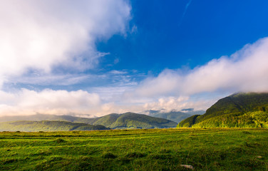 beautiful sunrise in mountains. gorgeous cloudscape above the ridge in the distance. clear grassy meadow on foreground