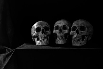 Old Three skulls put on the table which has black cloth cover in dim light room black and color for background