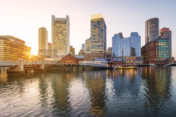 Boston Harbor and Financial District in Massachusetts, USA at sunset.
