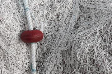 Gros plan de mailles de filet de pêche emmêlé sur un port avec un flotteur rouge et un espace vide sur la droite