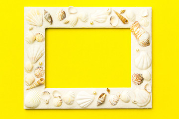 Photo frame with shells on  yellow color paper texture background. The concept of a summer vacation.  Summer Flatlay Image