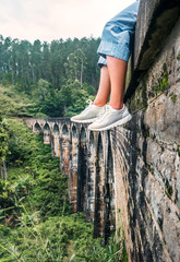 Female tourist sits on the Demodara nine arches bridge in Ella, Sri Lanka: close up feet image
