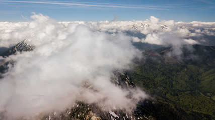 spring landscape with the mountain peaks covered with snow and clouds. aerial view by drone