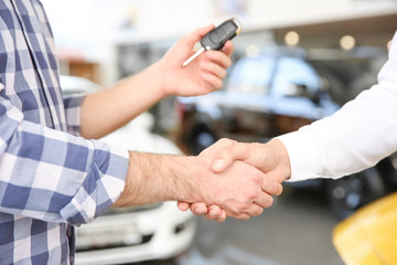 Young man shaking hands with salesman in car salon