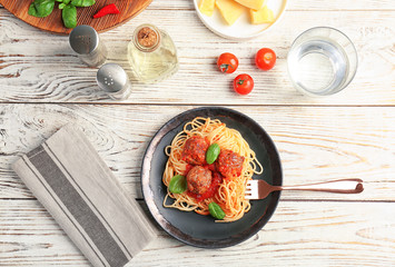 Delicious pasta with meatballs and tomato sauce on wooden background, flat lay