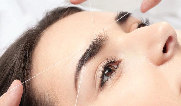 Young woman having professional eyebrow correction procedure in beauty salon, closeup